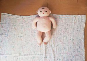 赤ちゃんをおくるみの上に寝かせる